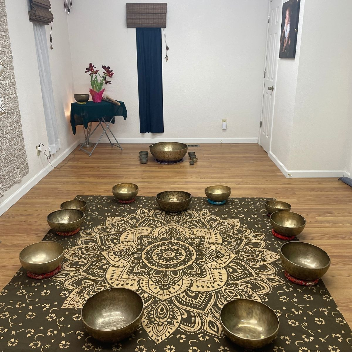 Singing bowls arranged on a heart laying on a brown mandala tapestry
