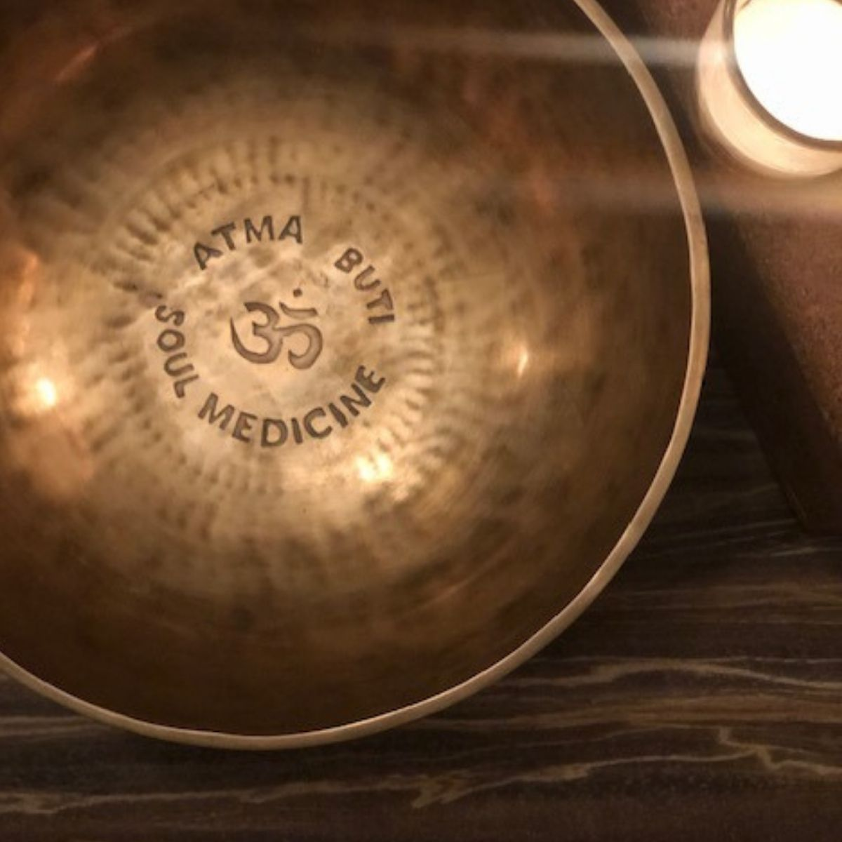 Singing bowl stamped with the words Atma Buti Soul Medicine and a lit candle.