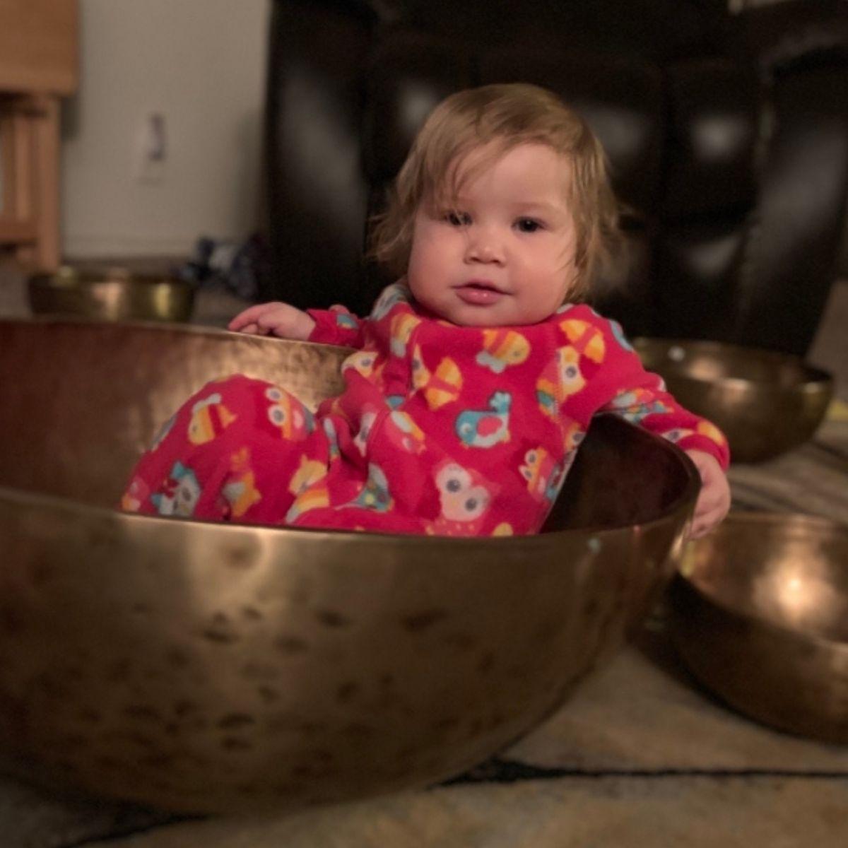 Baby wearing colorful pjs laying in a large healing singing bowl