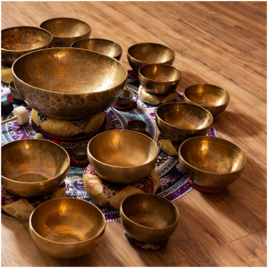 Numerous healing singing bowls on a color tapestry