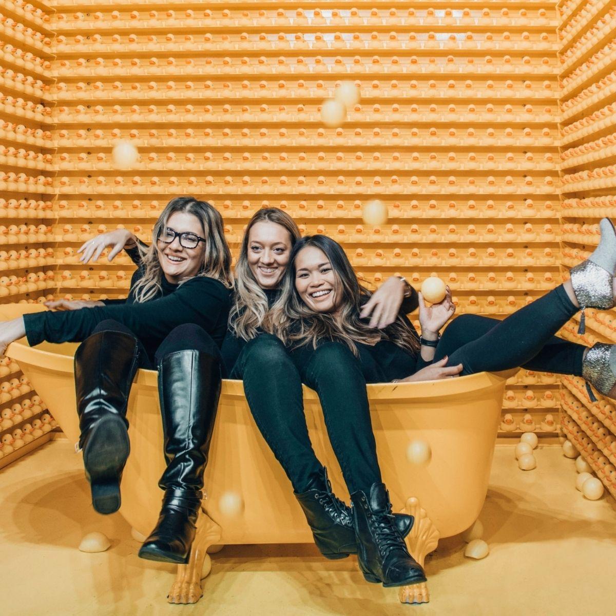 Three smiling females in a yellow bathtub