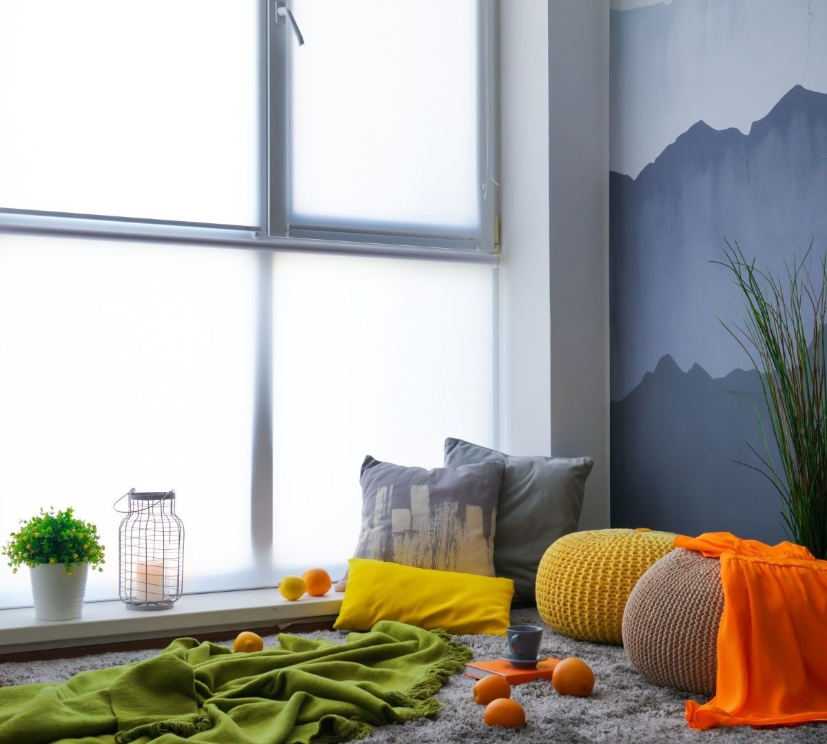 Space with a green blanket, pillows and oranges near a window.